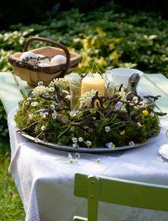 Auf dem Gartentisch ist ein rundes Gesteck mit einem Kerzenglas in der Mitte ein schöner Blickfang. Drumherum wird Moos zusammen mit verzweigten, kurzen Ästen und zarten Blüten arrangiert. Auch über das Fest hinaus ist das hübsche Ensemble eine Augenweide. (Foto: MSL/Kramp + Gölling)