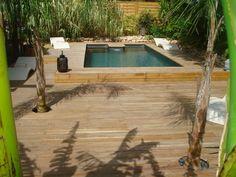 Piscine rectangulaire semi enterrée et terrasse en bois