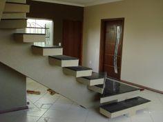 """Os arquitetos Matheus José Bigoni e Wanessa Mustafá Cristófano projetaram esta escada, tornando-a um elemento decorativo nesta casa em Dourados (MS). Por isso, ela foi feita """"em balanço"""", onde uma de suas extremidades é presa à parede e a outra é livre, e com degraus suspensos. Feita de concreto armado e granito verde, ela ainda é revestida com textura tipo grafiatto. O corrimão é de aço inox."""