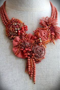 CORAL REEF Shades of coral, peach and just a hint of rose make this striking bib necklace perfect for spring and summer. Floral elements created from metallic silk organza and other fabrics are embellished with seed beads, coral beads and vintage faux coral beads. A few vintage faux pearls add to the mix for some contrast. Triple strands of vintage faux coral beads end with a length of vintage gold tone chain and a gold vermeil hook for adjustable length wear. Release your inner mermaid a...