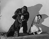 Gorilla Choking Man in The Monster and the Girl  Susan Webster (Ellen Drew) cowers in horror as a gorilla monster (Charles Gemora) chokes a man in the 1941 sci-fi horror film The Monster and the Girl. Photo still: John Springer Collection/ Corbis