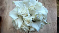 brides handtied bouquet of white roses, white calla lilies, and iridescent beading