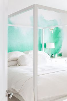 turquoise wall mural in an all-white, minimalist bedroom