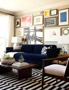 navy sofa and assorted art on neutral wall and a bold rug!