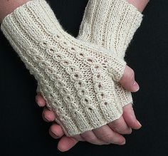 These fingerless gloves feature a decorative lace rib pattern that looks like strings of tiny cables on top of each mitt and a simple ribbing on the palm side for comfort. Cable needles and cable knitting experience is not necessary because the mock cables are actually created with a basic slipped stitch sequence followed by a yarn over in an easy to memorize five row pattern.