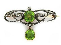 Peridot & Diamond Brooch  Art Nouveau (1890 -1915)  A decorative Art Nouveau piece with 20 eight-cut Diamonds set in Sterling Silver and backed with Gold and two large Peridots set in Gold.