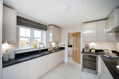 The kitchen's gleaming granite worktops are set off to perfection by accessories in silver and natural wood.