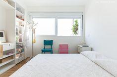 Quarto clean com cama baixa e estante metálica com tela que integra quarto e sala.