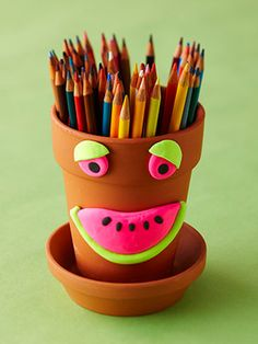 Decorate a flower pot with clay to make a grinning pencil holder.