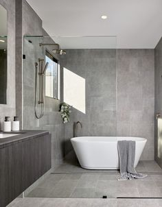 Large Metal Screens Provide Privacy For This New House Bathroom Ideas - In this modern bathroom, grey tiles cover the walls, while a seamless glass partition separates the shower and bathtub from the rest of the room. Grey Bathroom Tiles, Grey Tiles, Bathroom Renos, Modern Bathroom Design, Bathroom Flooring, Bathroom Interior Design, Bathroom Ideas, Bathroom Organization, Budget Bathroom