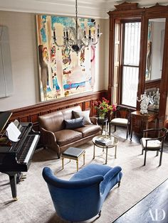 Oversized artwork in sitting area with piano and leather love seat