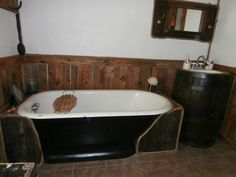 Old tub refurbished, whiskey barrel sink, sewing machine top with mirror , fence picket for wood decor on wall, added a little rope trim