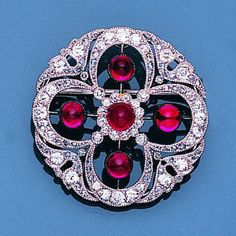 An belle époque ruby and diamond brooch, circa 1905 The circular brooch, pierced in a quatrefoil of millegrain-set old brilliant, single and rose-cut diamonds and cabochon rubies, one diamond deficient, diameter 3.0cm.