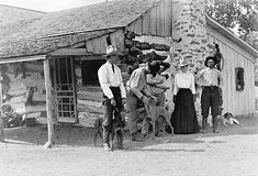 One cowgirl, four cowboys posed by old bunkhouse. Matador Ranch, Texas, 1908   Look at her fabulous hat...