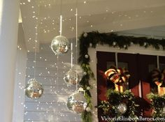 Disco Ball Hanging Decorations for the Front Porch for Christmas. So pretty mixed with greenery and love the sparkle when the sun hits it. Much better than just hanging regular ornaments!