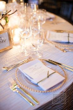 i like the table number with the gold frames. i also like how these glasses are set up. cava, red white white wine and water.