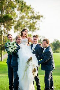 San Diego wedding at lomas santa fe country club groom and groomsmen navy blue suits with matching vests and white dress shirt with white bow tie and white floral boutonnieres carrying bride holding white floral bridal bouquet