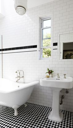A master bath with a clawfoot tub and black and white tiled floors | archdigest.com