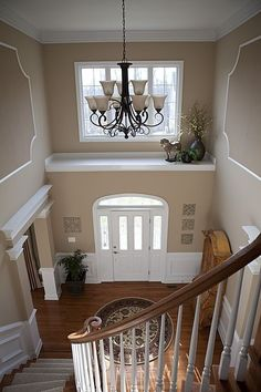 A traditional white door that compliments the trim and wainscoting makes this entrance warm and inviting.