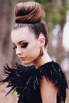 A top chignon, black dress & feathers. Gold earrings? Perfect accesory!