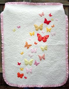Make an adorable blanket for a baby girl in no time with this simple baby quilt pattern made with butterfly appliques and a pink ruffle trim.