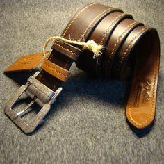 Уникальный кожаный двухсторонний ремень, выполненный в единственном экземпляре из двух полос кожи (коричневой и рыжей), склеенных и прошитых вручную крепким седельным швом. Аксессуар снабжен фирменной английской латунной пряжкой. На изделии вытеснен брендовый логотип мастерской.Роскошный подарок