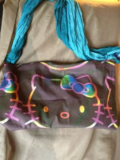Hello Kitty tote bag. Brown with a multi colored Hello kitty head. Blue zipper closure and a black nylon liner inside.