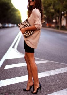 .Oversized knit top with a black mini skirt and pumps with a leopard clutch