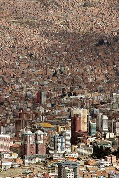 La Paz, Bolivia. The city sits in a bowl surrounded by high mountains of the altiplano. As it grew, La Paz climbed the hills, resulting in varying elevations from 10,500 to 13,500 ft. Overlooking the city is towering triple-peaked Illimani, which is always snow-covered and can be seen from several spots of the city. La Paz Metropolitan area, formed by the cities of La Paz, El Alto, & Viacha, make the most populous urban area of Bolivia. (V)
