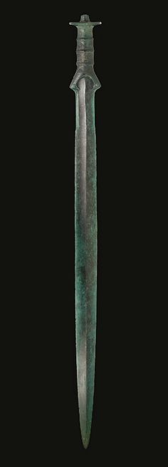 A EUROPEAN BRONZE SWORD  SOUTH-CENTRAL EUROPE, BRONZE AGE, CIRCA 12TH-10TH CENTURY B.C.   The lanceolate blade inserted into the separately-cast hilt, the blade with a peaked midrib, the edges serrated toward the hilt, lentoid in section, the baluster-shaped grip with three raised bands, incised with dotted scrolling and hatching along the length, the edges riveted on either side, the knobbed pommel incised with concentric circles and dots on the exterior, rows of dots on the underside