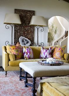 The velvet saffron-yellow sofa, chaise and ottoman were custom made and upholstered locally. The colorful throw pillows are covered with textiles collected during the couple's travels. The Tibetan hand-woven area rug is colored with vegetable dye for a natural gradation, and the antique lamps were purchased from the original owners of the home.