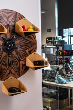 The base of the bookshelf is made from 6.5 mm thick CNC-cut plywood puzzles. Each puzzle is engraved with a laser. The whole set of 20 plywood puzzles placed in two rings around the center mechanism creates a tiger-like dimensional pattern. 3D printed parts include shelves, counterweights, a planetary gear mechanism, and the wall mounting.