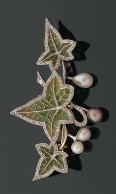 An Art Nouveau brooch, designed as a branch of ivy, consisting of gold, diamonds, pearls and plique à jour enamel. Circa 1890-1900.