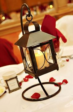 Simple lantern centerpiece with strewn red rose petals
