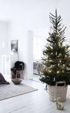 Standing the Christmas tree in a basket allows the sudden burst of colour to fit in around softer surroundings, while also exaggerating the traditional rustic feel.