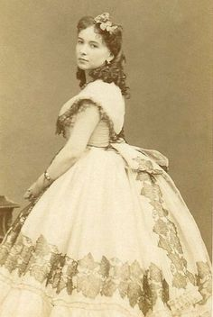 """Striking French beauty (and famed courtesan) Cora Pearl. [Assuming she is at the forefront of fashion, this dates probably from 1864, or possibly late 1863 or early 1865. The """"horned"""" hairstyle, slightly raised straight waist, and tiny sleeves are brand new. The skirt is still very full, however, and doesn't really show the new ellipitical shape.]"""