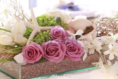 Beautiful wedding decoration made of pink roses blended with sea shell and star, green and white flowers. All perfectly sit in a glass box with sand Stock Photo - 28243929