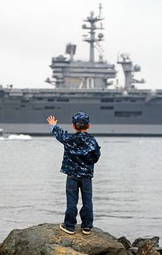 SAN DIEGO (Nov. 30, 2011) The son of Electrician's Mate (Nuclear) 1st Class Randall White, assigned to the Nimitz-class aircraft carrier USS Carl Vinson (CVN 70), waves to his father's ship as it transits San Diego Bay after departing Naval Air Station North Island on a scheduled deployment to the western Pacific region. (U.S. Navy photo by Mass Communication Specialist 2nd Trevor Welsh/Released)