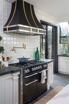 A Mercury stove sits on espresso stained wood herringbone floor between white shaker cabinets adorned with brass hardware and a black leathered granite countertop.
