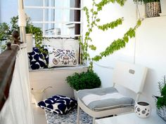 chic white balconies decorated with patterned cushions and white breeze-view.   Have white drop cloths with grommets and hooks on balcony walls  so  they can be put up or down depending on sun or \weather,