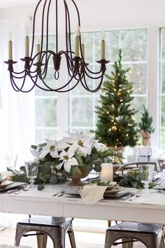 A Christmas table setting all ready for the season. Neutral color tones and farmhouse/cottage style decor. Dining room decor...