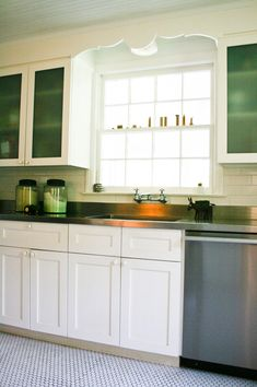detailed window molding + green frosted glass + stainless steel cabinets + hexagon tile floor in kitchen via Design Sponge