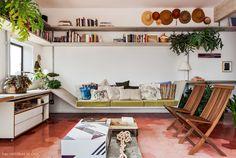 Sala de estar tem sofá e prateleiras feitos em concreto e piso hexagonal de ladrilhos hidráulicos.