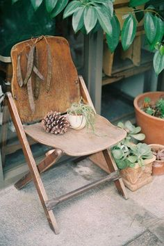 Give your outdoor partio space a rustic holiday cabin vibe by using folding wood chairs and decorating your outdoor space with greenery, potted plants, DIY eucalyptus wreaths and boughs, and sweet seasonal pinecone decor!