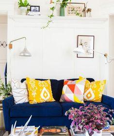 idée comment aménager un salon scandinave, canapé bleu marine, coussins jaunes e multicolores, mur couleur blanche, etagere murale, plantes vertes, piles de magazine et livres d art, decoration boheme en jaune et bleu