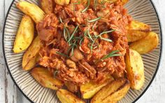 Young jackfruit is cooked in barbecue sauce and smoky spices until tender and easily shreddable, then served on a platter with oven-roasted potatoes.