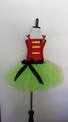 Super R Inspired Tutu Dress This beautiful Super R Inspired Tutu Dress will bring out the superhero of your little one. The tutu is made with lime green tulle, red tutu top, and black bow. The Top is