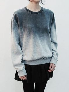 A woman is wearing an ombre sweater in a total black look