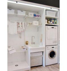 Ocupando a parede inteira, este móvel tem diversas funções - abriga pia, varais, máquinas de secar e lavar e prateleiras