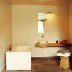Salle de bains avec baignoire-cube en résine, plan de toilettes en chêne